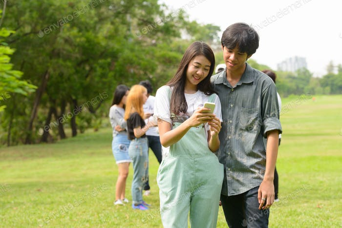 Happy young Asian couple using phone together with friends at the park