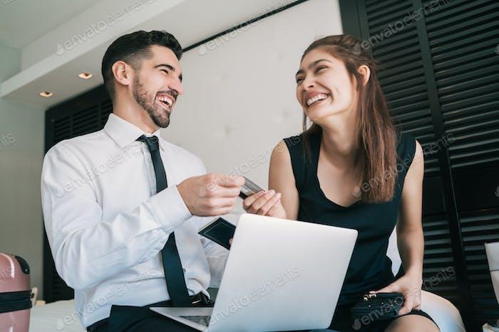 Zwei Geschäftsleute, die Kreditkarte für die Online-Zahlung verwenden.