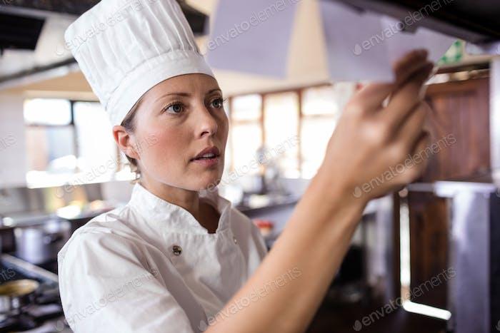 Chefkoch mit Blick auf die Bestellliste in der Küche