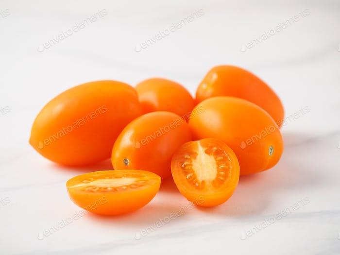 Orange tomatoes on white marble table