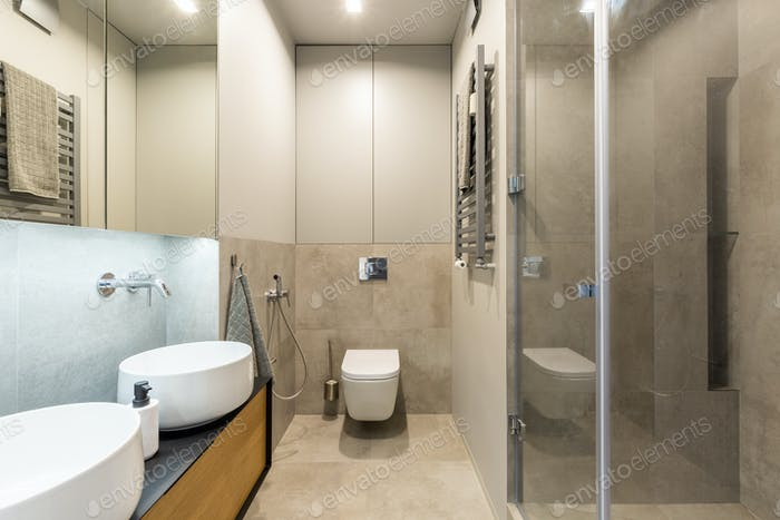 White toilet against beige wall in modern bathroom interior with