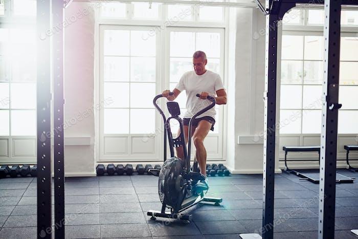 Konzentriert reifen Mann Reiten ein Gesundheitsclub stationäre Fahrrad