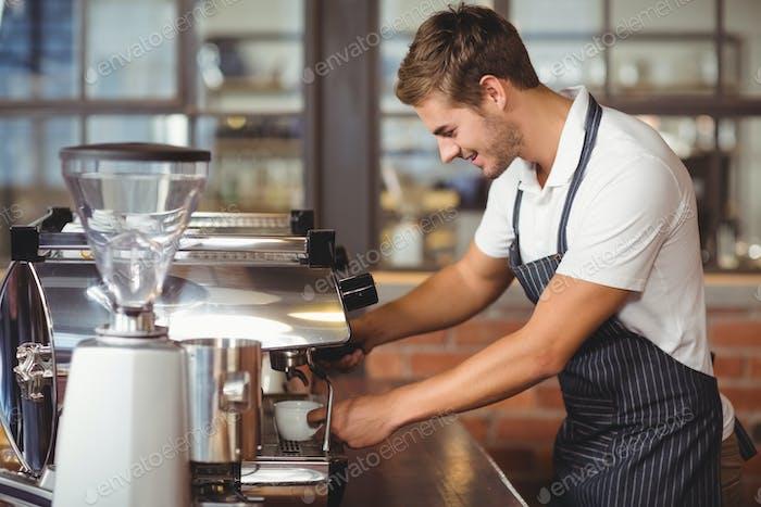 Hermoso barista haciendo una taza de café en la cafetería