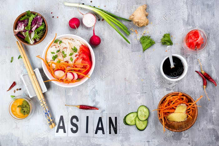 Asian rice noodles with vegetables and vegetarian salad on a plate on stone background