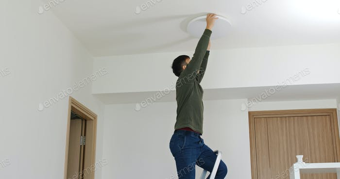 Man install lamp onto the ceiling at home