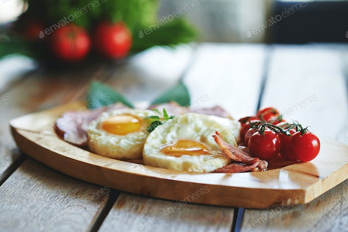 Breakfast - fried egg with bacon and vegetables on the wooden plate