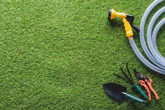 Draufsicht von Schläuchen, Handrechen, Spaten und Gartenschere auf Gras