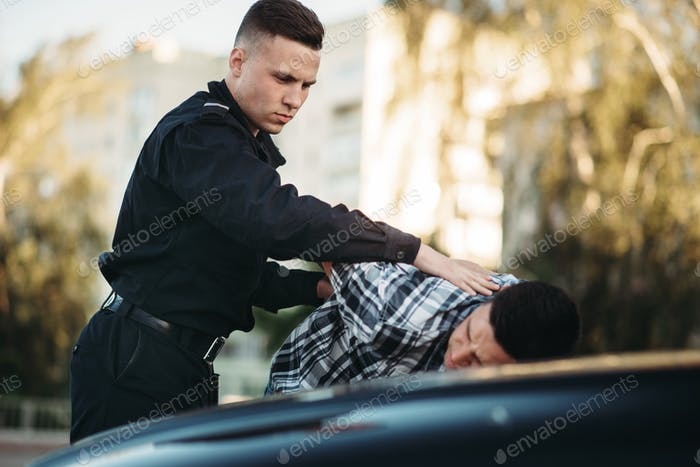 Police officer arrests the driver violator on road