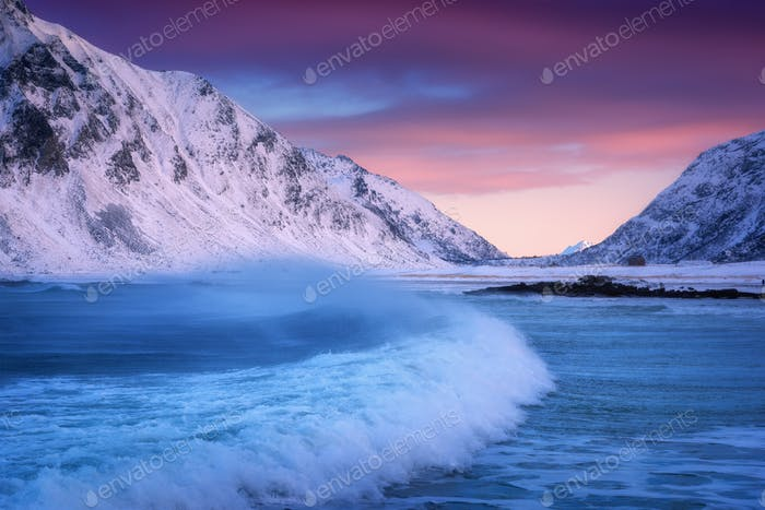 Sandy beach with blue sea and waves in winter at sunset