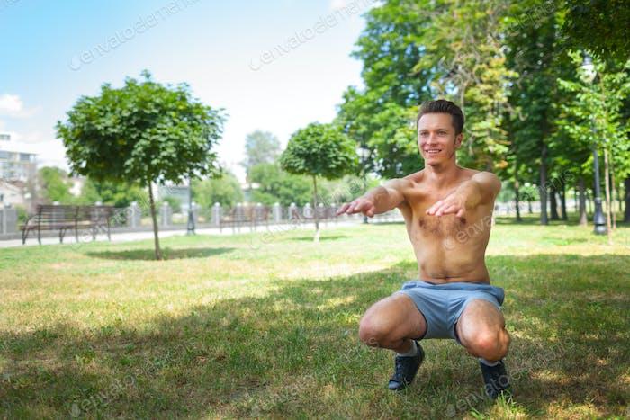 Shirtless Kerl tut Übung im Park