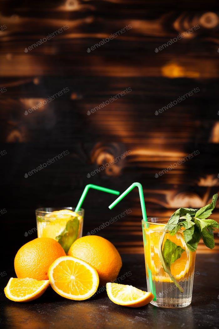 Delicous healthy orangeade on wooden background