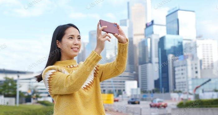 Frau fotografieren auf Handy in der Stadt