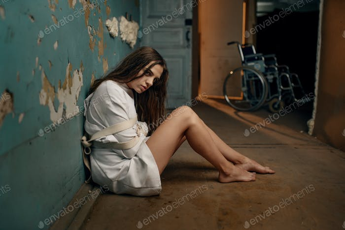 Mad patient in straitjacket sitting on the floor