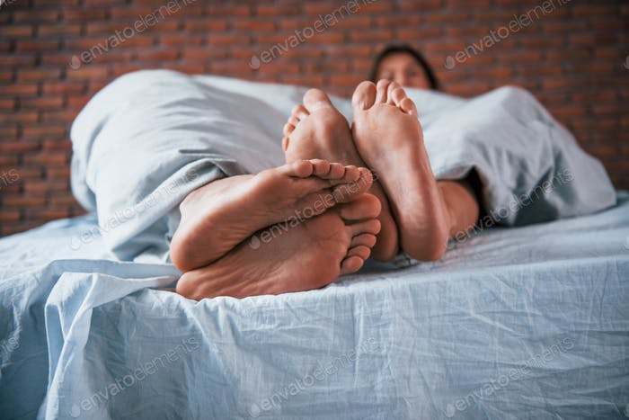 Close up view of foots of couple that sleeps together in the bedroom at morning time