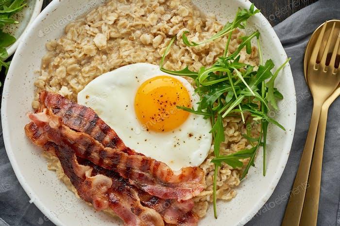 Haferflocken, Spiegelei und gebratener Speck. Gleichgewicht von Proteinen, Fetten, Kohlenhydraten. Ausgeglichenes Essen.