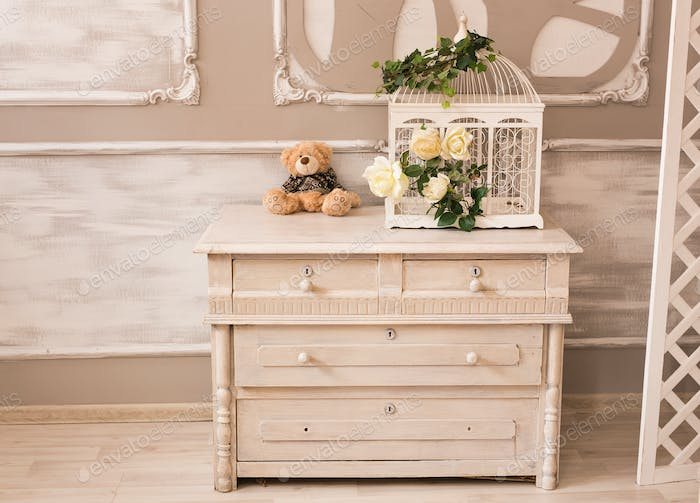 Classic interior of baby room with chest of drawers and teddy bear