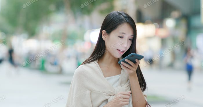 Woman sending audio message on cellphone in city