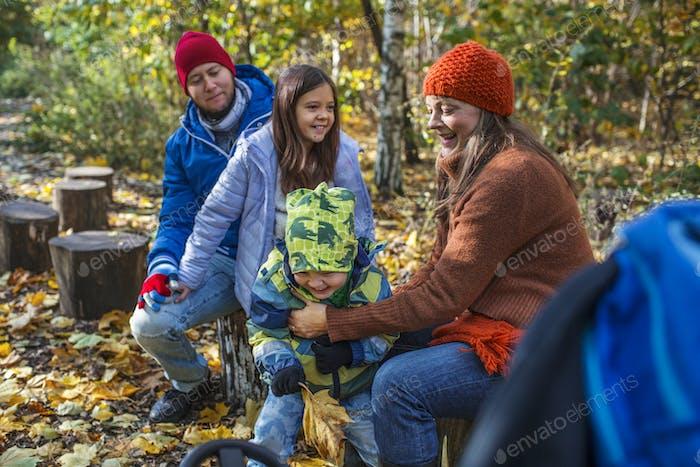 Счастливая семья из четырех человек проводит досуг в лесу