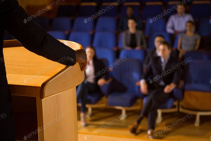 Mid section of male business executive giving a speech