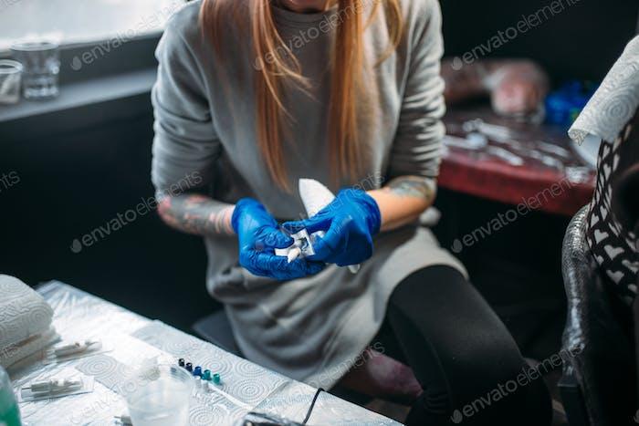 Weibliche Tätowiererin bereitet Tattoo-Maschine