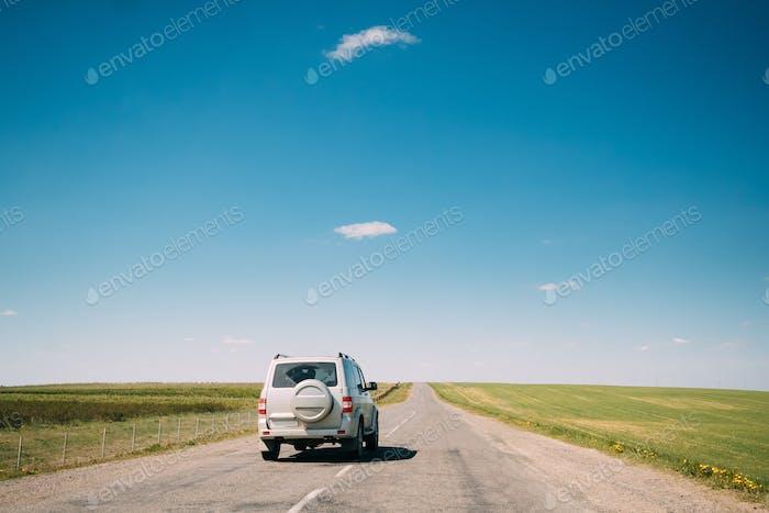 Gray SUV Car rides along Road In Spring Summer Fields Landscape
