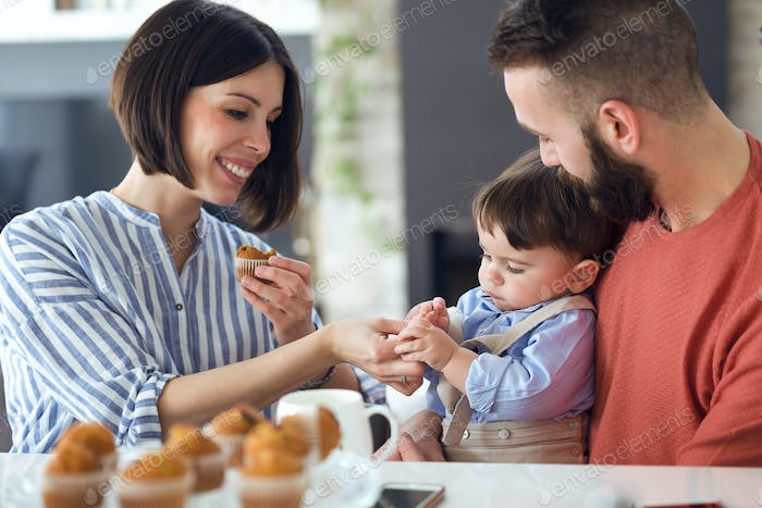 Beautiful young parents with they baby eating muffins at home.