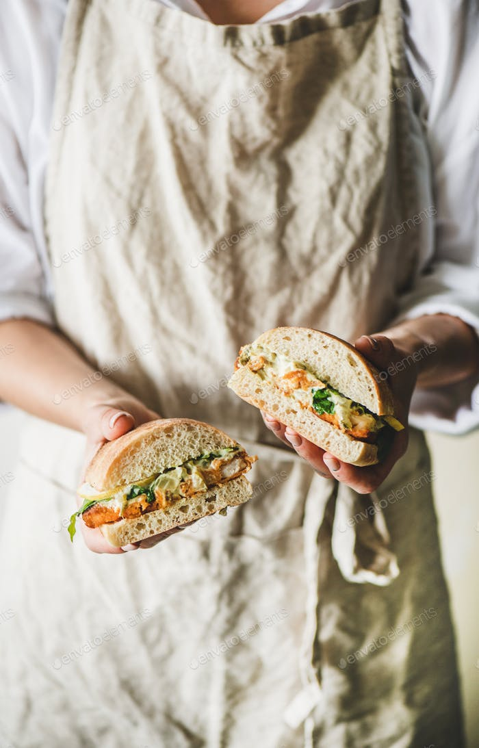 Woman holding fried fish sandwich with tartsre sauce, lemon, arugula