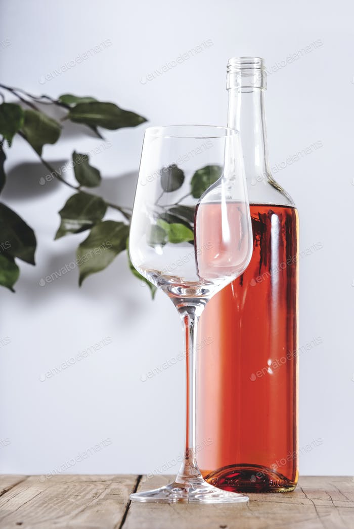 Rose wine glass with bottle on the white table