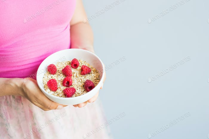 Woman's hands hold healthy and natural breakfast, oatmeal and raspberries in a bowl