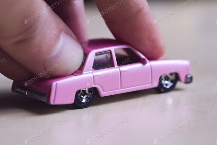 hand pushing a pink toy car