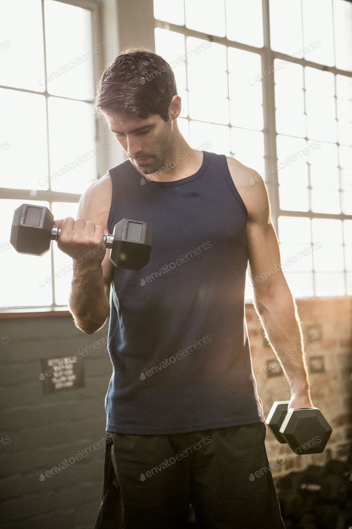 Man lifting dumbbell while looking down at the gym