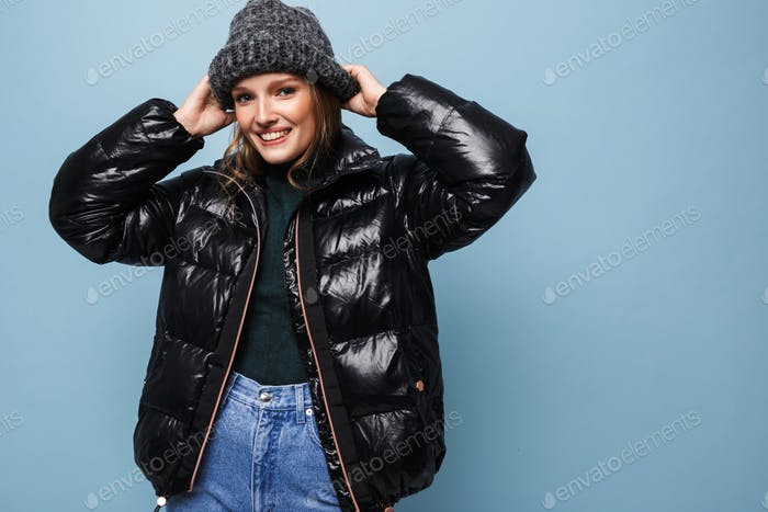 Young cheerful woman in knitted hat and black down jacket happily looking in camera