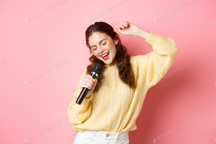 Carefree modern woman dancing and singing song in microphone, performing with mic, smiling and