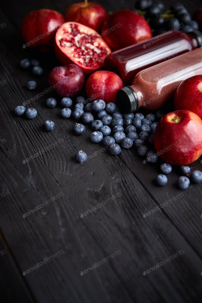 Various fresh red, purple black fruits. Mix of fruits and bottled juices on black