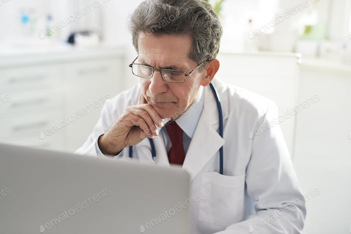 Senior doctor working with a laptop in doctor's office