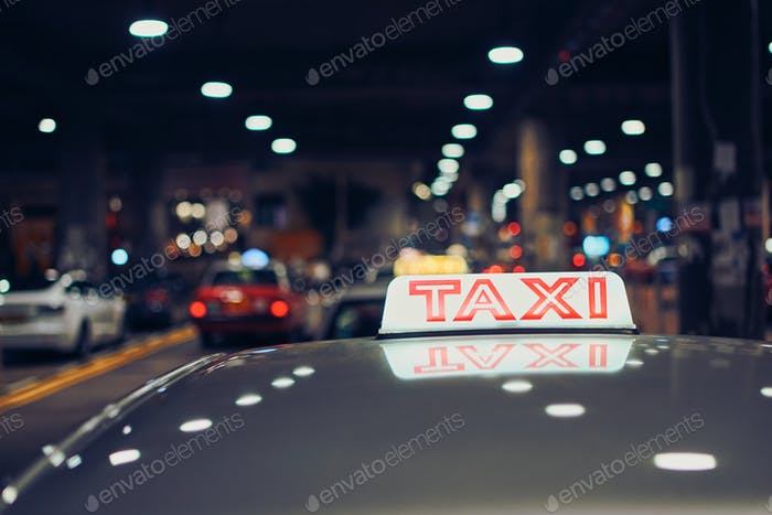 Taxi car on city street at night