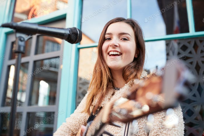 porträt von jungen weiblichen musiker busking spielen akustische gitarre und singen im freien in street