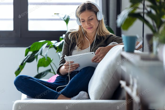 pretty young woman listening to music with her digital tablet on sofa at home.