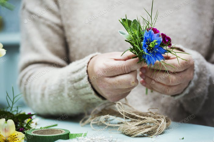 A florist working, creating a small posy.