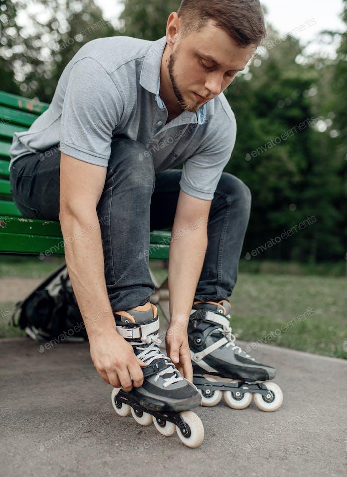 Roller skating, male skater puts on skates in park