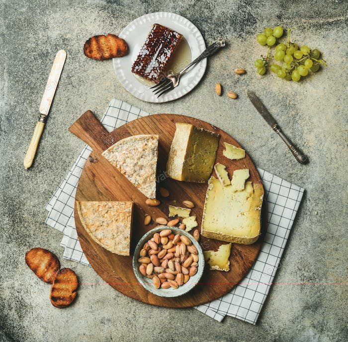 Flat-lay of cheese platter with cheese assortment and snacks