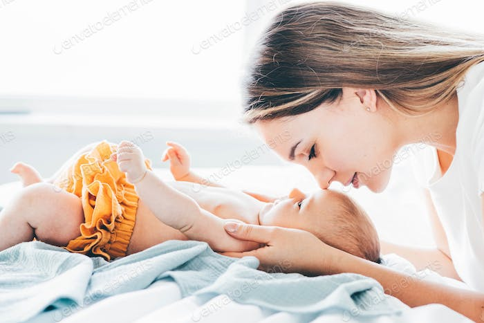 Mother and her newborn baby together at home.