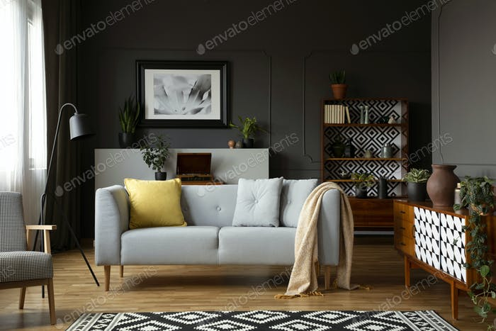Blanket and pillows on grey settee in retro living room interior
