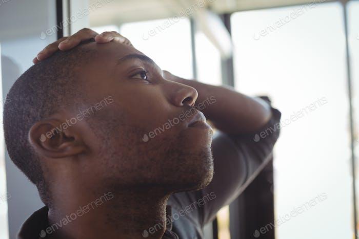 Sorgen Geschäftsmann lehnte sich auf Glas im Büro