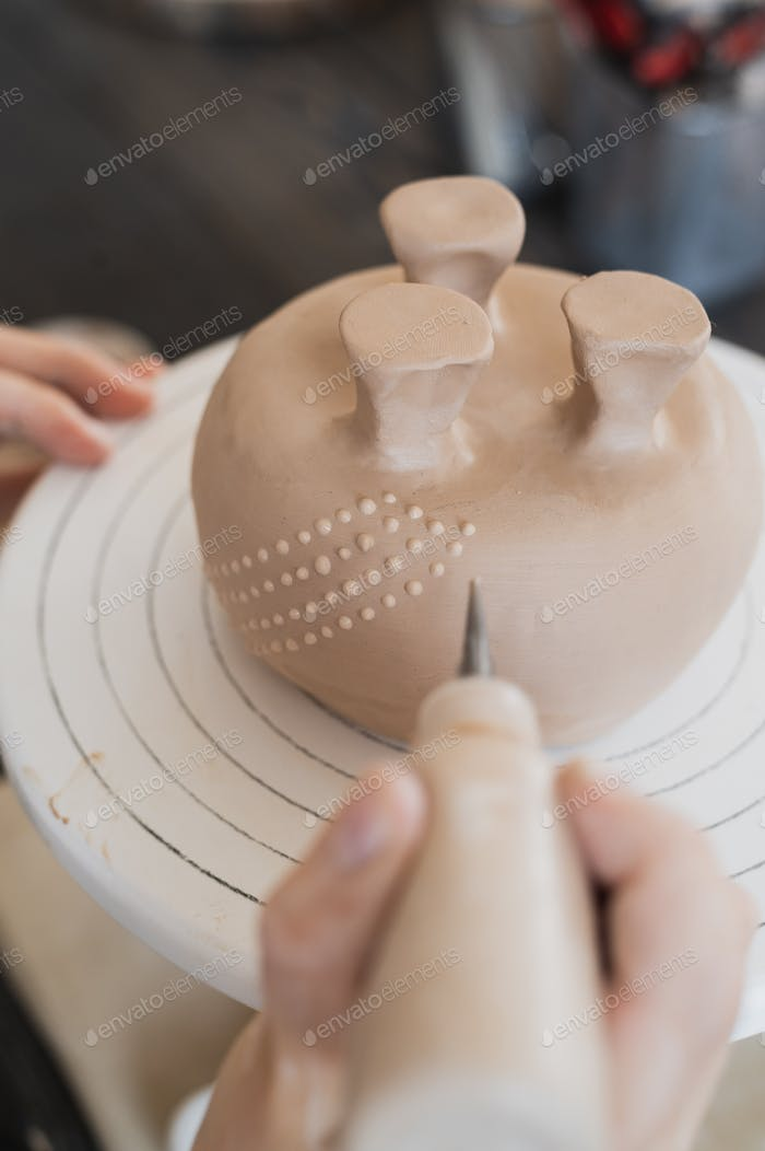 Child in the process of decorating the clay vase. Children pottery studio