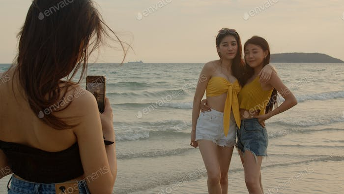 Asian women using mobile phone photography and playing on beach, Beautiful female relax on beach.