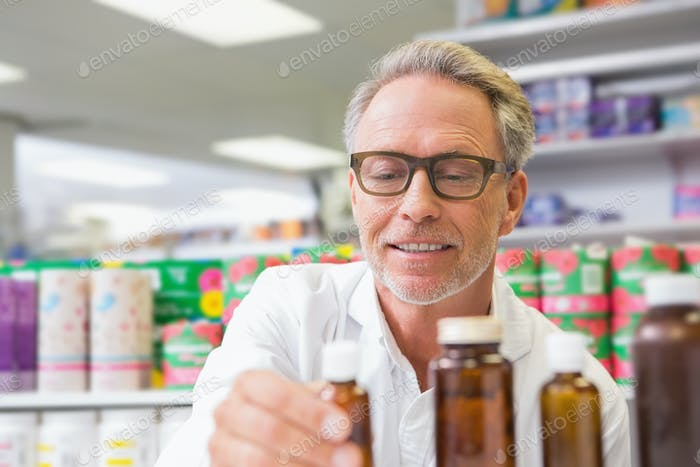 Senior holding and looking at jar of medicine in the pharmacy