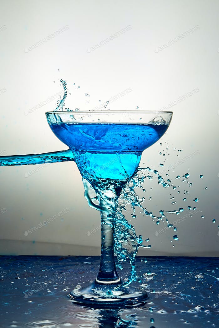 Glass with blue champagne or cocktail. Levitation