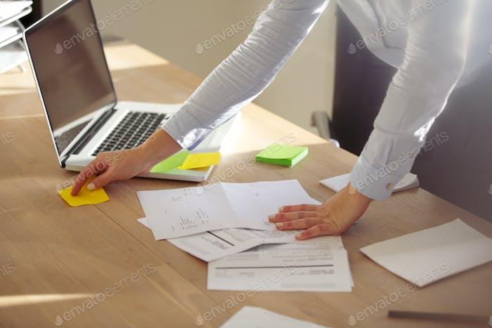 Geschäftsfrau überprüft Notizen auf posten es