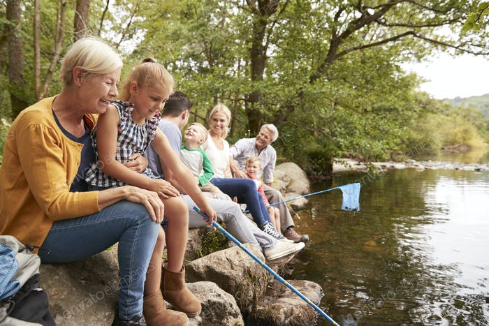 Multi Generation Family Fishing With Nets In River In UK Lake District